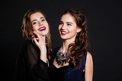 Two happy women in  black cocktail dresses. Two beautiful women in elegant black cocktail dresses celebrating Royalty Free Stock Image