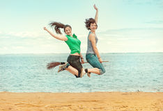 Two happy women with broom jumping on the beach Stock Photos