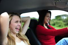 Two happy women in a car. Two happy young women driving in a car stock photos