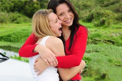 Two happy women on car trip. Hugging and laughing stock photography