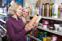 Two happy women chooses shampoo Stock Photography