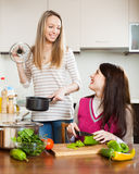 Two happy women cooking something. Together at them kitchen stock photography