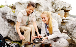 Two happy women cooks outdoors. Two friendly women cook up some food while camping in the wilderness. outdoor hiking lifestyle concept stock photos