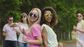 Two happy women dancing with friends at pool party, enjoying life, slow motion. Stock footage stock video