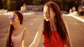 Two happy women with dreads walking on the empty road and talking in summer. Two hipster girls laughing and dancing stock video footage
