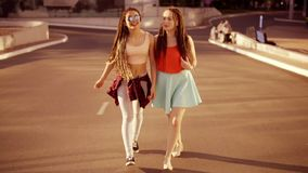 Two happy women with dreads walking on the empty road and talking in summer. Two hipster girls laughing and hugging each stock footage