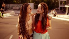 Two happy women with dreads walking on the empty road and talking in summer. Two hipster girls laughing, hugging and. Kissing each other during a bright sunny stock video