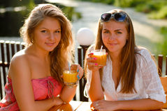 Two happy women drinking orange juice Stock Photography