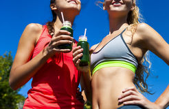 Two happy women drinking vegetable smoothie after fitness runnin Royalty Free Stock Photo