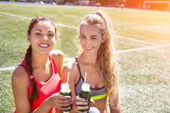 Two happy women drinking vegetable smoothie after fitness runnin Stock Images