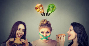 Two happy women eating hamburgers looking at stressed chubby girl with measuring tape around her mouth and junk food and vegetable. S light bulbs above head royalty free stock image