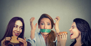 Two happy women eating hamburgers looking at stressed girl with measuring tape around her mouth. Royalty Free Stock Photos