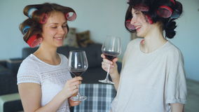 Two happy women friends with funny curler hairstyle drink wine and talk at home. Two happy women friends with funny curler hairstyle drink wine and talk stock video footage