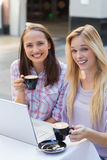 Two happy women friends looking at camera with cup of coffee Stock Images