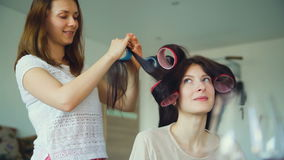 Two happy women friends make fun curler hairstyle each other and have fun at home. Two happy women friends make fun curler hairstyle each other and have fun in stock footage