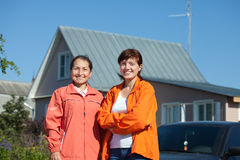 Two happy women  in front of  residence Royalty Free Stock Photos