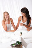 Two happy women having fun with champagne Stock Images