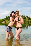 Two happy women having fun at lake in summer Royalty Free Stock Images