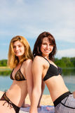 Two happy women having fun at lake in summer Stock Photography