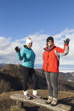 Two happy women hikers waving hello outdoors Stock Photography