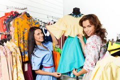Two happy women holding blue skirt in the shop Royalty Free Stock Photos