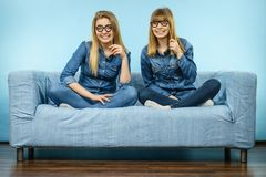 Two happy women holding fake eyeglasses on stick. Having fun fooling around wearing jeans shirts. Photo and carnival funny accessories concept Stock Photography