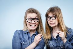 Two happy women holding fake eyeglasses on stick. Having fun fooling around wearing jeans shirts. Photo and carnival funny accessories concept Stock Image