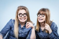 Two happy women holding fake eyeglasses on stick Royalty Free Stock Image