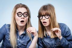 Two happy women holding fake eyeglasses on stick Royalty Free Stock Photo