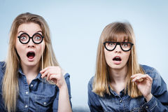 Two happy women holding fake eyeglasses on stick. Having fun fooling around wearing jeans shirts. Photo and carnival funny accessories concept Royalty Free Stock Image