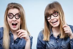 Two happy women holding fake eyeglasses on stick Stock Photos
