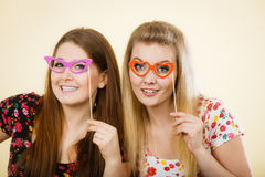 Two happy women holding fake eyeglasses on stick. Having fun wearing tshirts with flower pattern. Photo and carnival funny accessories concept Royalty Free Stock Image