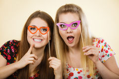 Two happy women holding fake eyeglasses on stick. Having fun wearing tshirts with flower pattern. Photo and carnival funny accessories concept Royalty Free Stock Photos