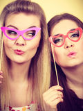 Two happy women holding fake eyeglasses on stick. Having fun wearing tshirts with flower pattern. Photo and carnival funny accessories concept Stock Images