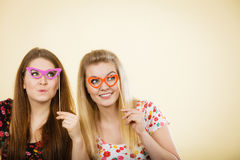 Two happy women holding fake eyeglasses on stick. Having fun wearing tshirts with flower pattern. Photo and carnival funny accessories concept Stock Photos