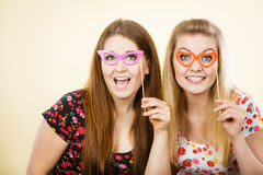Two happy women holding fake eyeglasses on stick. Having fun wearing tshirts with flower pattern. Photo and carnival funny accessories concept Royalty Free Stock Photo