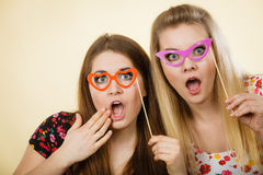 Two happy women holding fake eyeglasses on stick. Having fun wearing tshirts with flower pattern. Photo and carnival funny accessories concept Royalty Free Stock Images