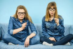 Two happy women holding fake eyeglasses on stick. Having fun fooling around wearing jeans shirts. Photo and carnival funny accessories concept Royalty Free Stock Photos