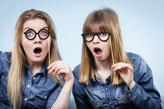Two happy women holding fake eyeglasses on stick. Having fun fooling around wearing jeans shirts. Photo and carnival funny accessories concept Royalty Free Stock Photography