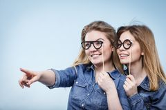 Two happy women holding fake eyeglasses on stick Royalty Free Stock Images