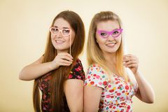 Two happy women holding fake eyeglasses on stick. Having fun wearing tshirts with flower pattern. Photo and carnival funny accessories concept Royalty Free Stock Photography