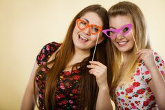 Two happy women holding fake eyeglasses on stick. Having fun wearing tshirts with flower pattern. Photo and carnival funny accessories concept Stock Photography