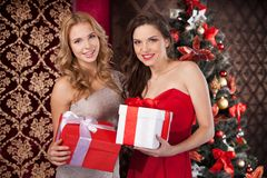 Two happy women holding gift boxes. Royalty Free Stock Photo