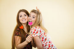 Two happy women holding heart on stick Stock Photo