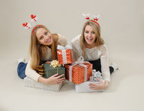Two happy women hug heap of gift boxes Royalty Free Stock Images