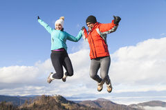 Two happy women joyfully jumping outdoors Stock Photos