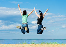 Two happy women jumping on the beach Stock Photography