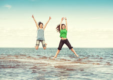Two happy women jumping in the water of sea Stock Photo
