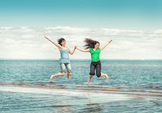 Two happy women jumping in the water of sea Stock Photography