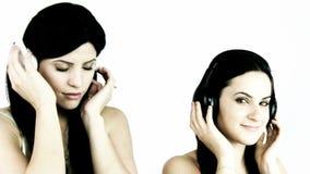 Two happy women listening music stock video footage